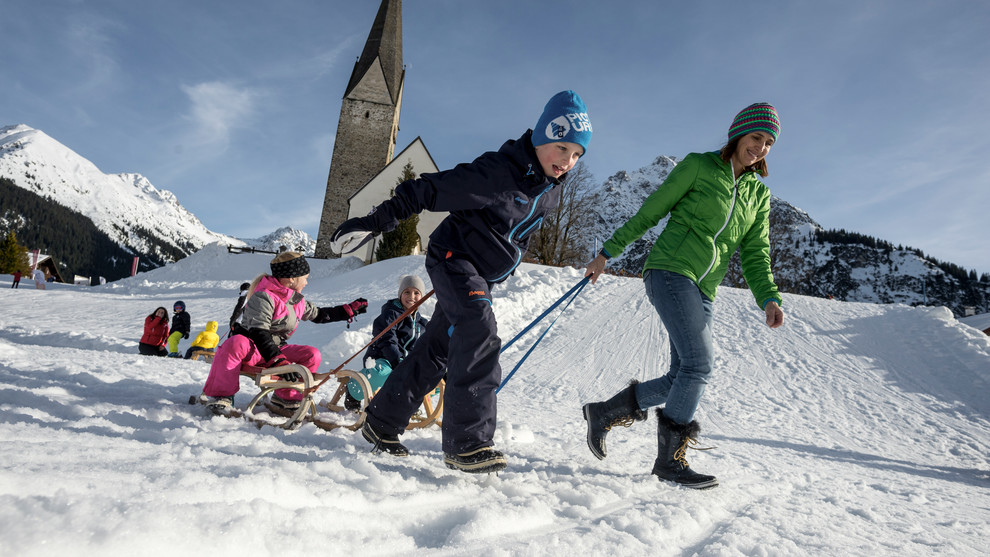 Family at sledding | © Kleinwalsertal Tourismus eGen | Photographer: Dominik Berchtold