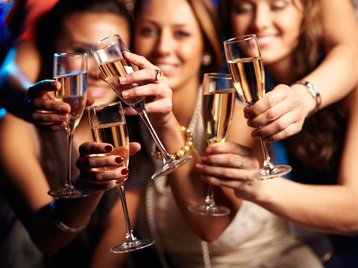 Group of partying girls clinking flutes with spark